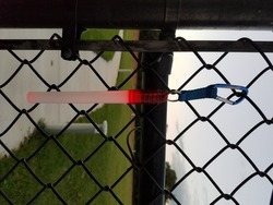 pink or red glowstick handing on metal fence
