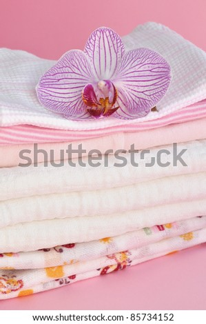 Pink orchid on a pile of folded baby clothes