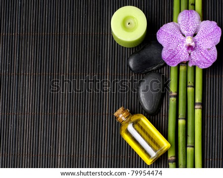 Pink orchid with thin grove and stones with candle on mat