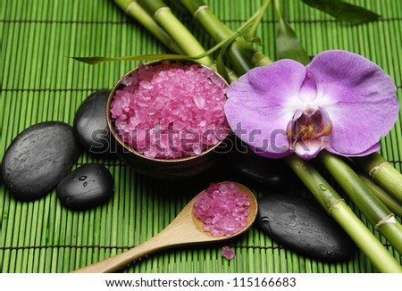 Pink orchid, with zen stone and sea salt in spoon  and groveon mat