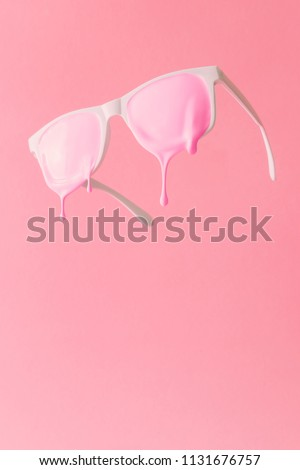 Pink paint dripping out of white painted sunglasses. Creative fashion minimal concept.
