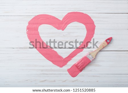 pink painted heart with paintbrush on white wooden background
