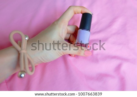 Pink Painted Nails. Beautiful Pink Nail Manicure with Pink Bottle in Woman is Hand on Pink Background Great for Any Use. #1007663839