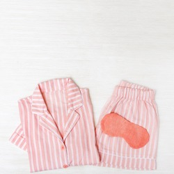 Pink pajamas for Girls, eye mask for sleeping on white wood. Top view. Flat lay.