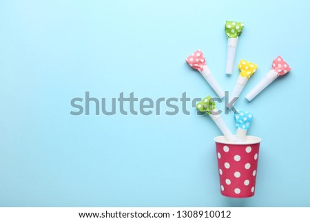 Pink paper cup with blowers on blue background