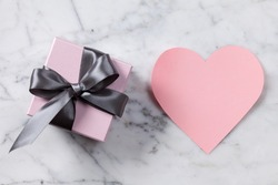 Pink paper heart and gift box on a marble table