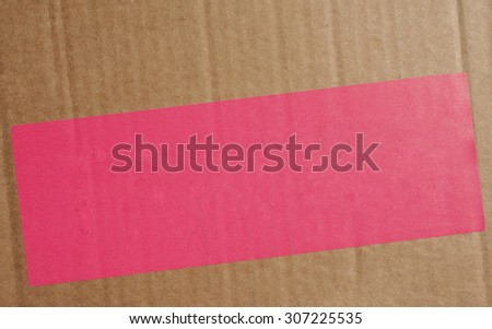 Pink paper tag or label or sticker for product information on a corrugated cardboard box packet