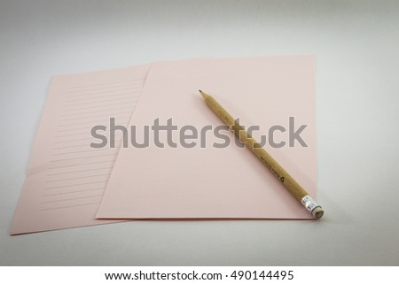 pink papers and pencil on white backgrounds