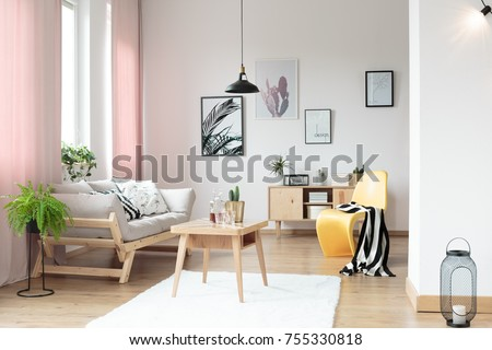 Pink pastel curtains in living room and yellow designer chair #755330818