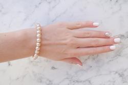 Pink pearl bracelet worn on a woman's pen, beautiful white manicure