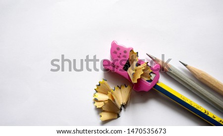 Pink pencil sharpener and pencil on a white background.