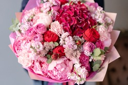Pink peonies and red hydrangea. Beautiful bouquet of mixed flowers in woman hand. Floral shop concept . Handsome fresh bouquet. Flowers delivery. Red and pink color.