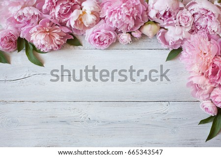 Pink peonies and roses on a wooden background #665343547