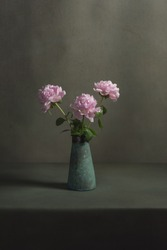 Pink peonies in a vintage pottery vase on a table in a grey room.