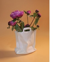 Pink peonies in an abstract porcelain vase stylized as a bag. Free space. Card