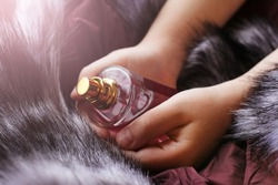 Pink perfume in a child's hand on a fur so close