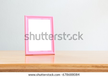Pink photo frame on wooden table over white wall background