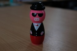 Pink Pig Figure with Sunglasses and Tuxedo Suit on Wooden Desk Table, Kids Toy, Macro Close Up