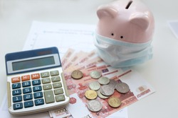 Pink piggy Bank in a medical mask and russian rubles money . Economic fight against the Coronavirus