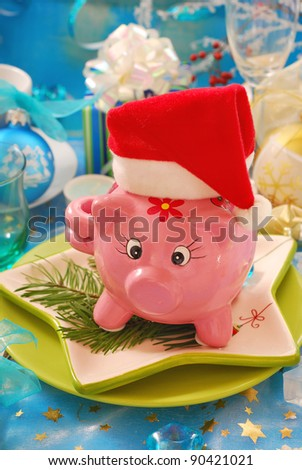 pink piggy bank in santa hat on christmas table