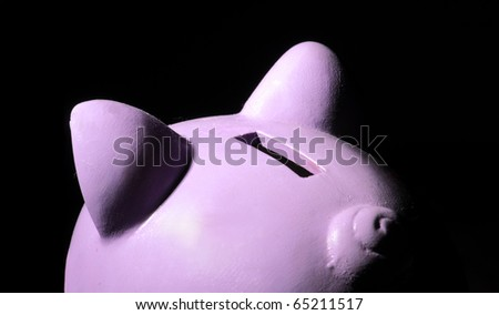 Pink piggy bank on black background. - stock photo