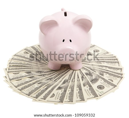 Pink piggy bank on dollars