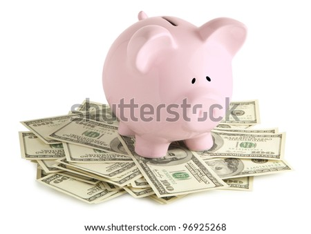 Pink piggy bank on dollars