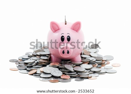 Pink piggy bank sitting in pile of coins stares out at viewer