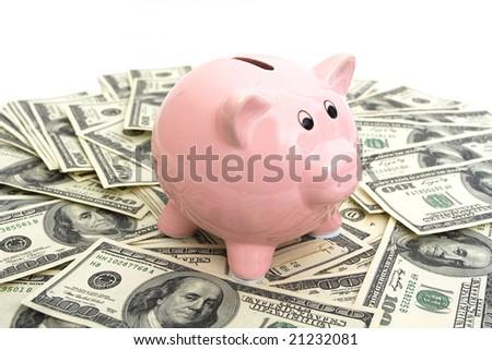 pink piggy bank sitting on top of hundred dollar bills