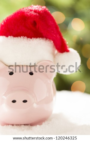 Pink Piggy Bank Wearing Red and White Santa Hat on Snowflakes with Abstract Green and Golden Background. - stock photo