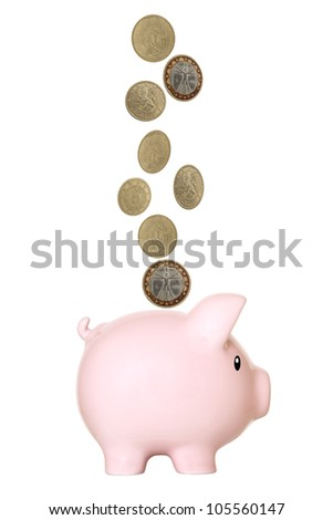 Pink piggy bank, with euro coins falling into slot. Isolated