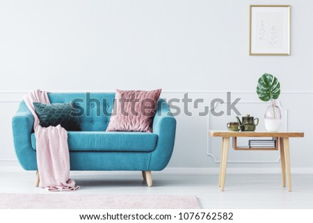 Pink pillow on turquoise couch next to wooden table in pastel living room interior with poster