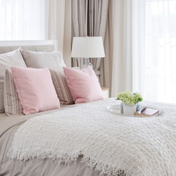 pink pillows on bed with white tray of flower at home