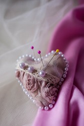 Pink pincushion heart on a light background. Handmade.
