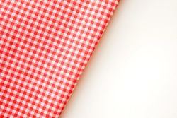 Pink plaid fabric or tablecloth on white background with copy space.