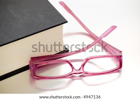 Pink plastic glasses close to a black book. - stock photo