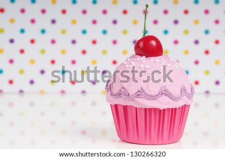 pink princess cupcake with cherry on top on a dotted background. birthday card design.