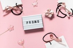 Pink promo sale banner with text Promo on the lightbox, shining decorations, gift boxes and bags with ribbons. Festive sale concept.