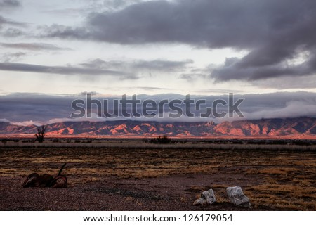 Pink-red color of winter dawn sunlight paints mountains in rural high desert/Dark Pink Sunrise Color on Mountain Range in Winter Semi-Desert Landscape/Winter sunup spotlights desert mountain range