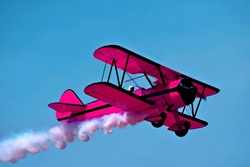 Pink retro airplane biplane isolated on sky background. Fashion vintage old airplane fly & female pilot. Pink airplane & white smoke. Airplane biplane condensation trail, smoky effect line after plane