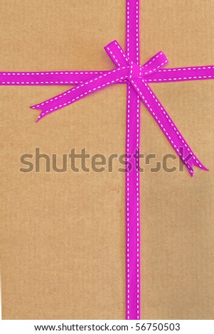Pink ribbon and bow on cardboard as background with space for text