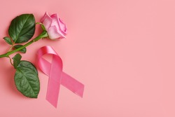 Pink ribbon and rose on pink background. Breast cancer awareness month concept