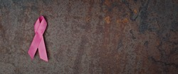 Pink ribbon breast cancer awareness symbol on grunge background. Panoramic image with copy space.