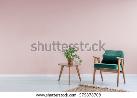 Pink room with green armchair, rug and side table
