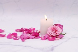pink rose and white candle isolated in marble background