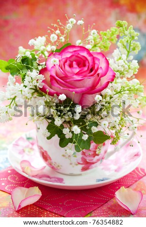 Pink rose and white lilac in a cup