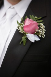Pink rose boutonniere flower on groom's wedding coat