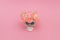 Pink rose flower in decorative Skull Planter on pink background. Minimal romantic love concept. Human Skull Head Design Flowers Pot with beautiful Rose blossoms. Halloween skull head with flowers