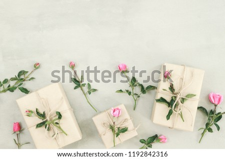 Pink rose flowers, gift box or present on gray stone table from above in flat lay style. Present with flower Greeting for Womens or Mothers Day. Top view, above