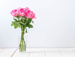 pink rose in vase on wood background with copy space